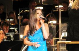 Girl in a blue dress singing at the Symphony Idol